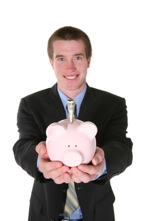 accrue: A hansome business man holding a piggy bank with money (Focus on Piggy Bank)