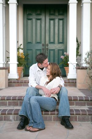 young couple kissing: A young couple kissing in front of their new home Stock Photo