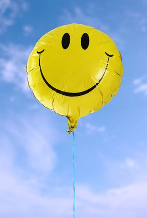 elated: A smiley faced balloon in the blue sky
