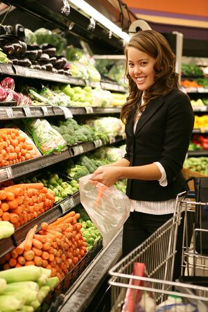 A pretty woman shopping for vegetables in the supermarket photo