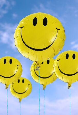 A smiley faced balloon in the blue sky