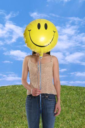 A woman holding a smiley face balloon under the blue sky