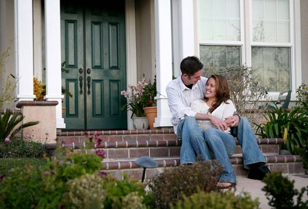 An attractive couple relaxing in front of their home Stock Photo