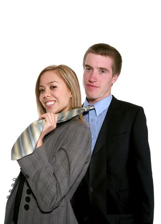 A businesswoman pulling on the necktie of a businessman