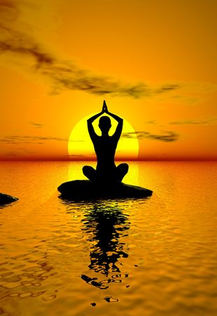 A silhouette of a woman on a rock doing yoga at sunset photo