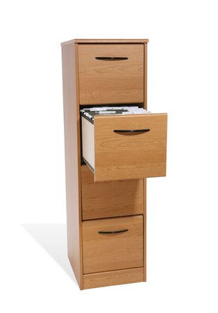 A tall wooden file cabinet with one drawer open Stock Photo