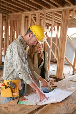 carpenter's sawdust: A home designer working with a home buildering and inspecting the blueprints