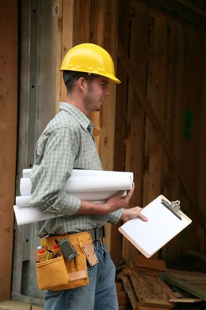 carpenter's sawdust: A home contractor holding blueprints outside a home in progress