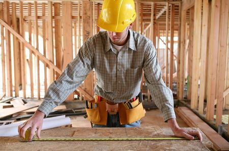 carpenter's sawdust: A man working building a home and measuring some wood