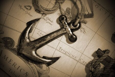 maritime: An anchor attached to rope over a vintage map