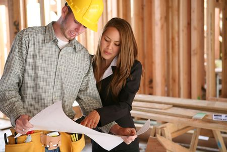 A home designer working with a home buildering and inspecting the blueprints Stock Photo - 804660