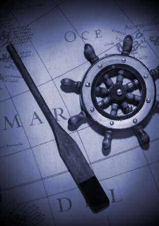 oar: An old oar and ships steering wheel over a vintage map