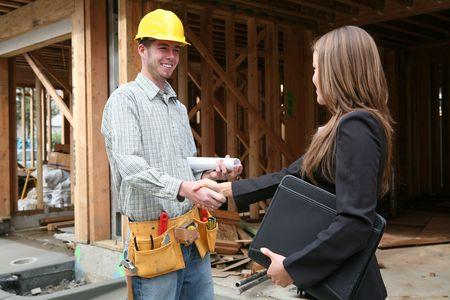 constructeur: Une femme propri�taire serrant la main avec le travailleur de la construction  Banque d'images