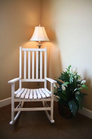 A room with a rocking chair in a home interior photo