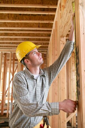 A man working building a home and measuring some wood Stock Photo - 804722