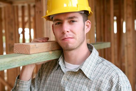 carpenter's sawdust: A handsome construction man carrying some wood