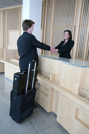welcome desk: A business man arriving in the lobby for a sales meeting Stock Photo