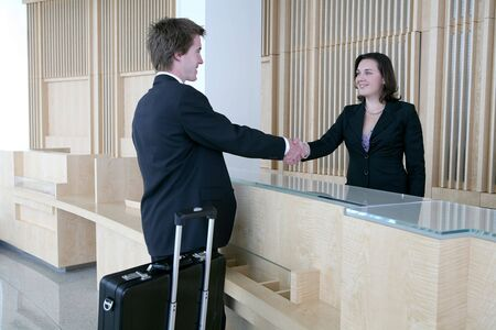hotel receptionist: A business man arriving in the lobby for a sales meeting Stock Photo