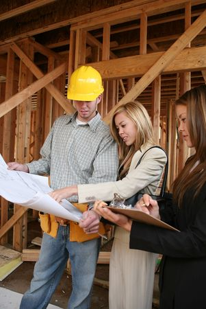 home builder: Two real estate agents working with a contruction home builder Stock Photo
