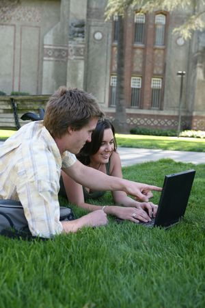 sidewalk talk: Two students studying on the grass with a laptop computer