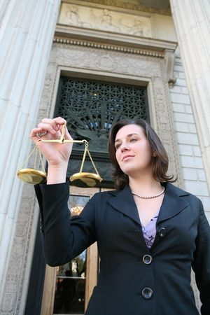 impartial: A pretty lawyer holding justice scales outside a courthouse