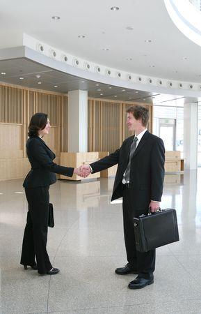 An attractive business man an woman shaking hands Фото со стока