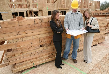 home builder: Two real estate agents and a home builder discussing the blueprint
