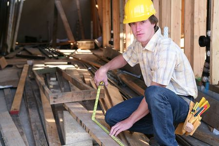 carpenter's sawdust: A construction man working building a home and measuring some wood