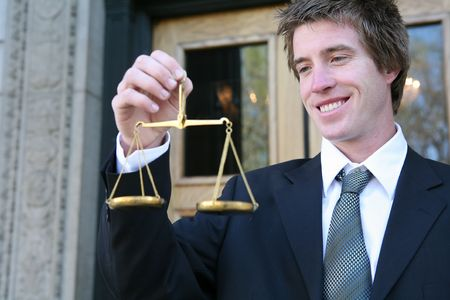 A business man holding a justice scale outside the court building