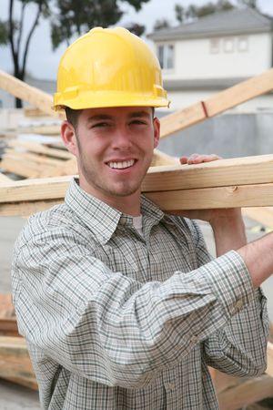 A handsome construction man carrying some wood