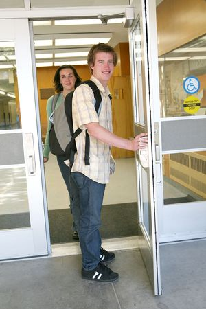 schoolhouse: Two students (Man and woman) leaving school after obtaining an education Stock Photo