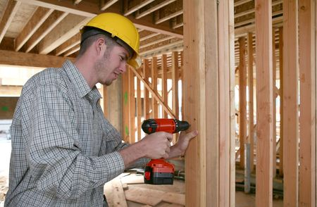 A handsome construction man using a drill to secure a beam photo