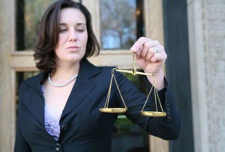 balanza justicia: Una mujer de negocios la celebraci�n de una escala de la justicia fuera de la corte edificio (Enfoque en parte con escala)