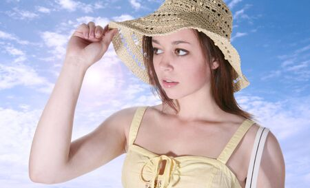 A pretty young woman adjusting her hat under the bright outdoor sun photo