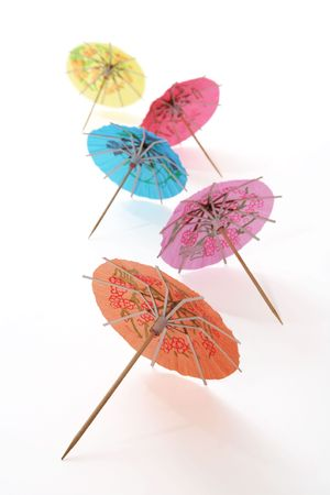 toothpick: Several colorful cocktail umbrellas over white with toothpick