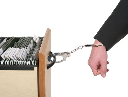 A business man handcuffed to a file cabinet isolated over white photo