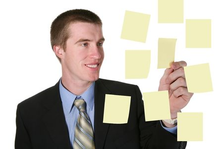A handsome business man pulling a post-it note off the board photo