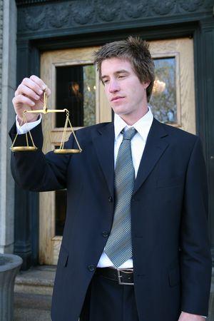balanza justicia: Un hombre de negocios que sostiene una escala de la justicia fuera del edificio de la corte