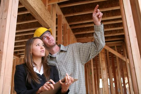 A home construction worker pointing out something for the client