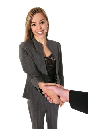 A young, cute business woman shaking hands in agreement isolated over white
