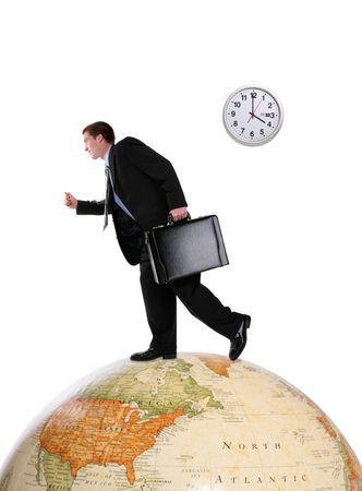 to hasten: A handsome business man running on a world globe