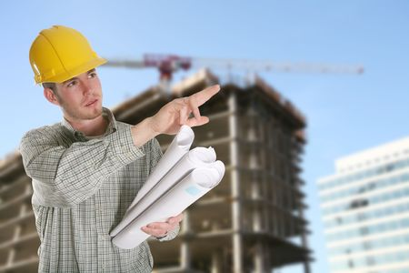 A construction worker with a building and crane in the background photo