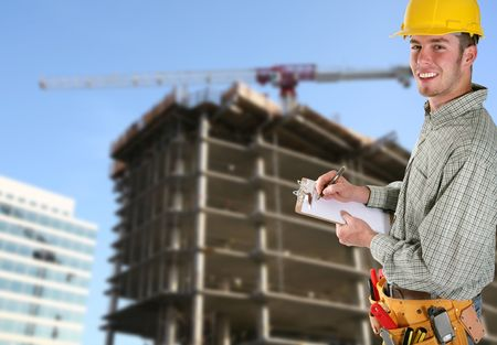 A handsome contruction worker taking noted isolated over white photo