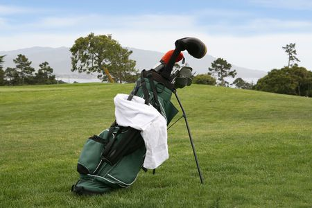 A golf bag with gold clubs on a beautiful golf course Фото со стока