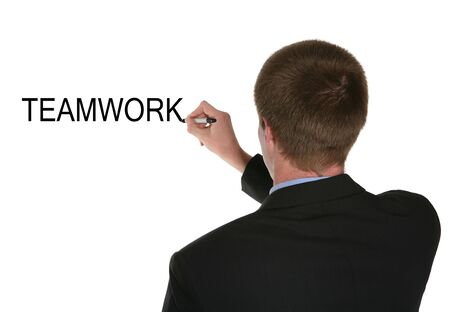 teaming: A business man writing the word teamwork on the board