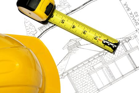 erecting: A hard hat and tape measure on a blueprint for new architecture