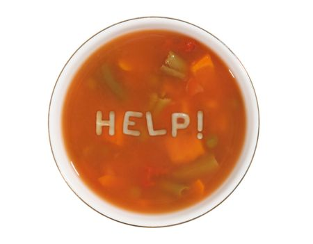 A bowl of alphabet soup with the word help spelled out Reklamní fotografie