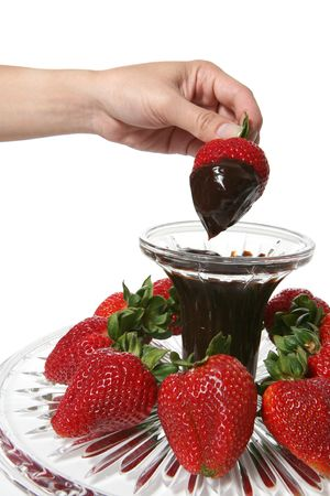 A woman dipping a strawberry into a bowl of chocolate Stock Photo