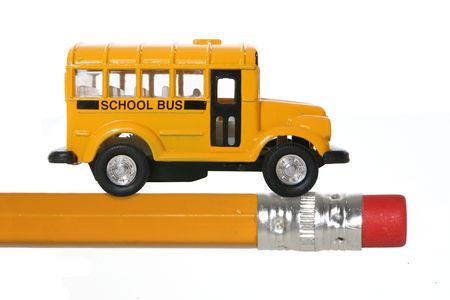 A yellow school bus on a pencil representing an education theme photo