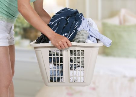 domestic task: Woman holding the dirty laundry in the bedroom